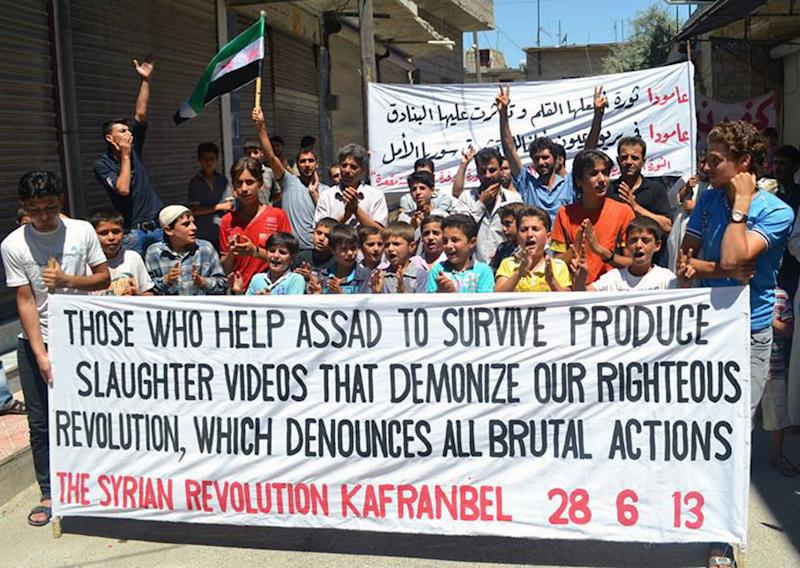 This citizen journalism image provided by Edlib News Network, ENN, which has been authenticated based on its contents and other AP reporting, shows anti-Syrian regime protesters holding a banner at Kafr Nabil town in Idlib province, northern Syria, Friday, June 28, 2013. Intense shelling by Syrian government troops on a village in the country's south killed several women and girls overnight as forces loyal to President Bashar Assad pushed ahead with an offensive against rebels near the border with Jordan, activists said Friday. (AP Photo/Edlib News Network ENN)