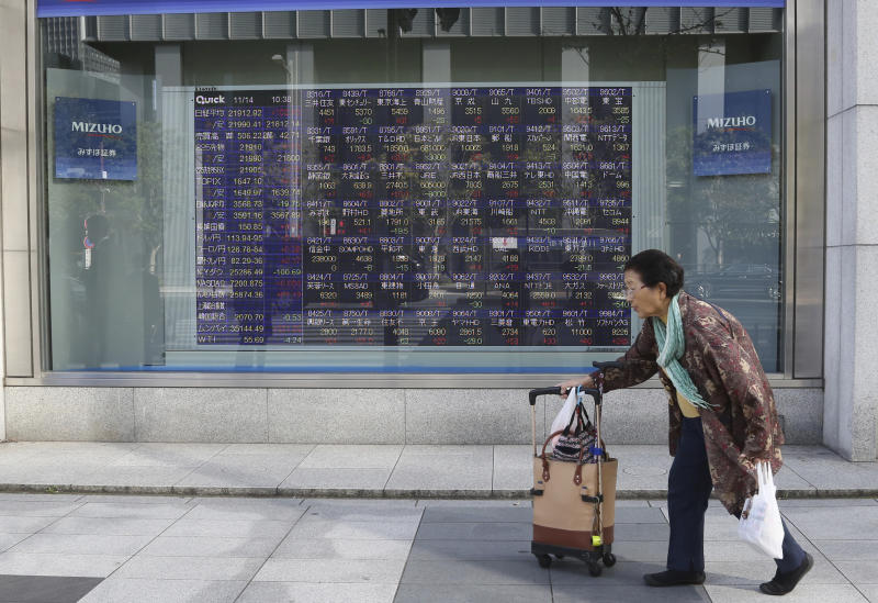 A woman walks by an electronic stock board of a securities firm in Tokyo, Wednesday, Nov. 14, 2018. Asian shares were mostly lower Wednesday, after the steepest drop in oil prices in more than three years put investors in a selling mood on Wall Street. (AP Photo/Koji Sasahara)