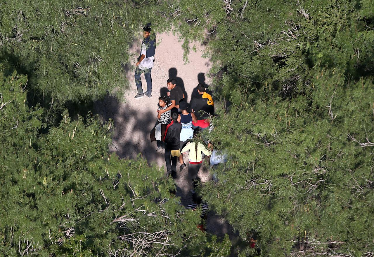 <p>Undocumented immigrant families walk before being taken into custody by Border Patrol agents on July 21, 2014, near McAllen, Texas. (Photo: John Moore/Getty Images) </p>