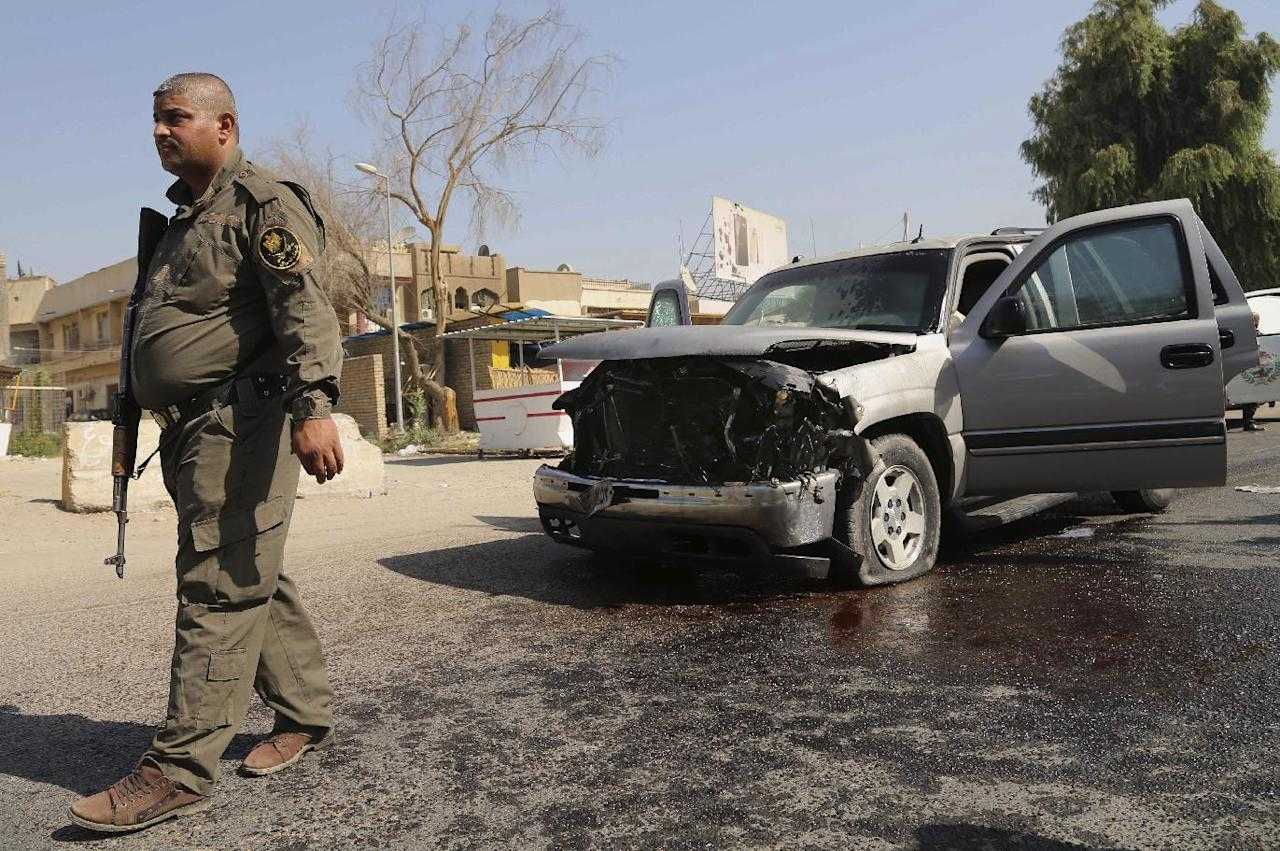 A policeman guards next to a damaged armored sport utility vehicle following a bomb blast at Baghdad's northern Azamiyah neighborhood, Iraq, Sunday, Sept. 15, 2013. A blast targeting the head of Baghdad's provincial council in the capital's northern Azamiyah neighborhood killed at least two and wounded at least eight, police say. The council head escaped unharmed. (AP Photo/Khalid Mohammed)