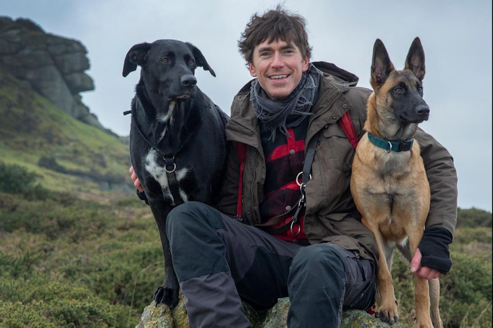<p>Explorer Simon Reeve with his two dogs in Dartmoor</p> (Westley Hargrave)