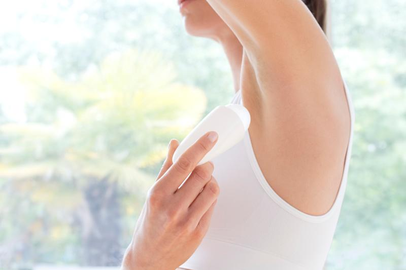 MODEL RELEASED. Young woman applying underarm deodorant, close up.