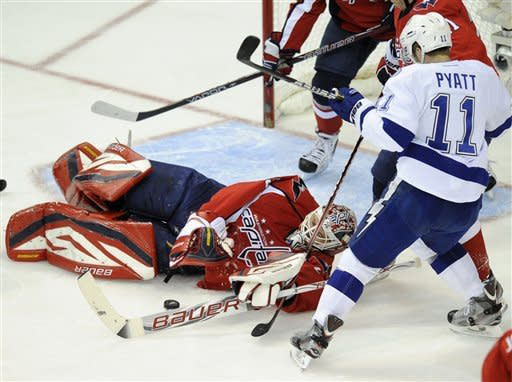 Washington Capitals goalie Tomas Vokoun (29), of the Czech Republic, reaches for the puck against Tampa Bay Lightning left wing Tom Pyatt (11) during the first period of an NHL hockey game, Thursday, March 8, 2012, in Washington. (AP Photo/Nick Wass)