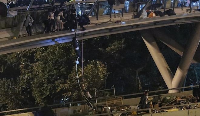 Some of those trapped inside PolyU abseil down to a highway. Photo: Felix Wong