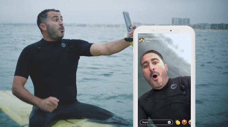A man on a surfboard filming himself with his phone.