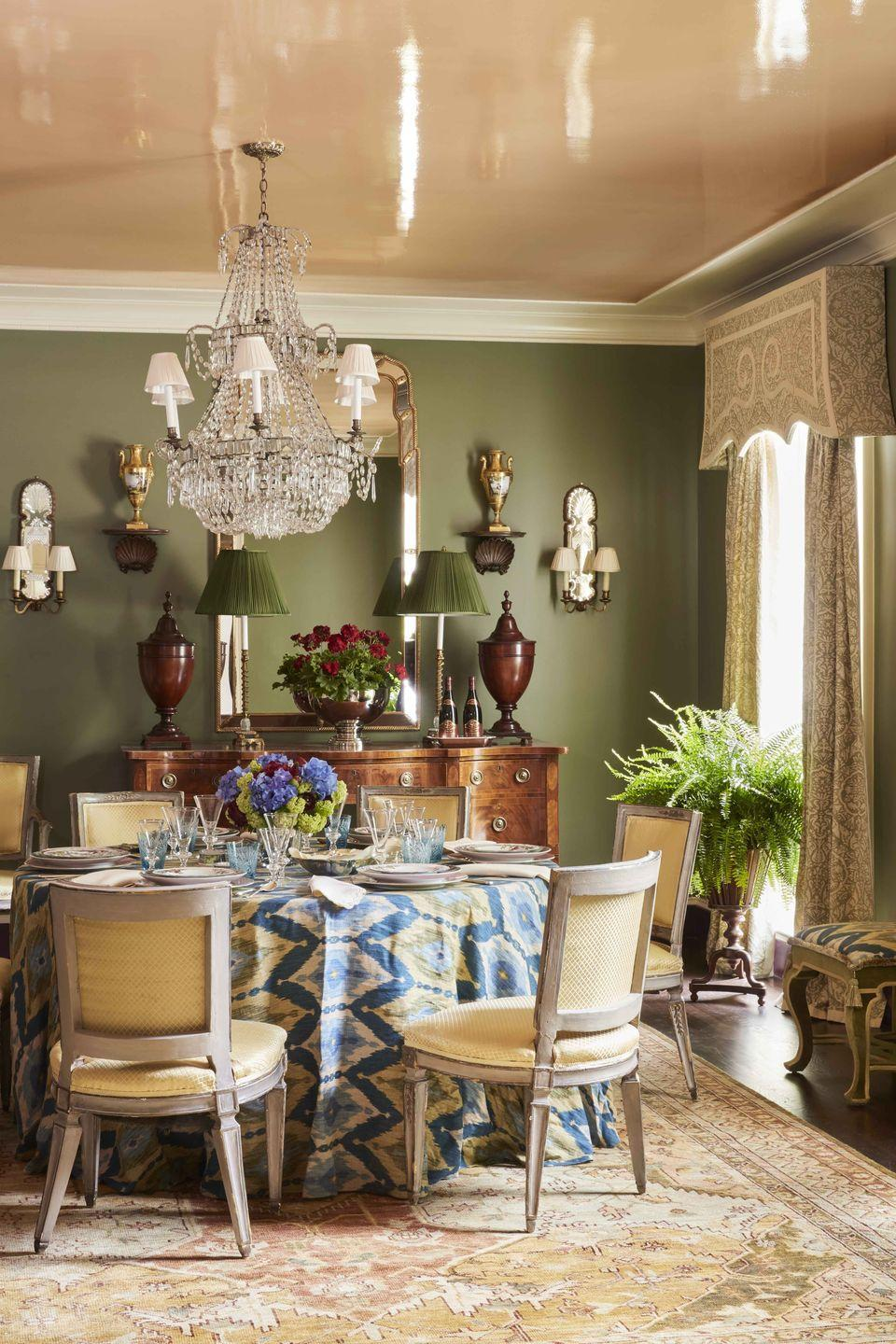 """<p>The apricot lacquered ceiling of designer <a href=""""https://danielledrollins.com"""" rel=""""nofollow noopener"""" target=""""_blank"""" data-ylk=""""slk:Danielle Rollins's"""" class=""""link rapid-noclick-resp"""">Danielle Rollins's</a> Atlanta dining room casts a flattering glow. The walls are painted <a href=""""https://www.farrow-ball.com/en-us"""" rel=""""nofollow noopener"""" target=""""_blank"""" data-ylk=""""slk:Farrow & Ball's"""" class=""""link rapid-noclick-resp"""">Farrow & Ball's</a> silvery Ball Green, and the curtains are in a <a href=""""https://fortuny.com"""" rel=""""nofollow noopener"""" target=""""_blank"""" data-ylk=""""slk:Fortuny"""" class=""""link rapid-noclick-resp"""">Fortuny</a> fabric. </p>"""