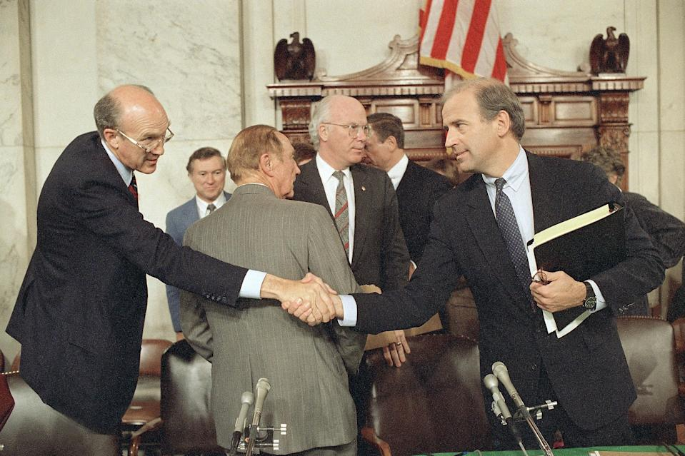 Senate Judiciary Chairman Joseph Biden, D-Del., right, and Sen. Alan Simpson, R-Wyo., shake hands after the committee voted not to recommend the confirmation of Supreme Court nominee Robert Bork, Oct. 7, 1987. Directly behind are Sens. Strom Thurmond, R-S.C., back to camera, and Patrick Leahy, D-Vt. (Photo: John Duricka/AP)