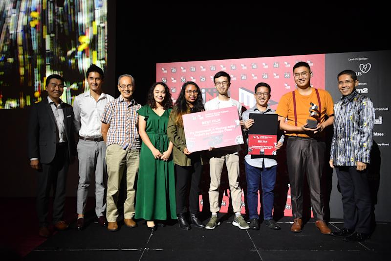 """Senior Minister of State for Defence and Foreign Affairs Maliki Osman (right) with Jastine Tan (in orange), winner of the ciNE65 Movie Makers Awards for the film """"My Homeland: A Photography Project by Grandpa Chen"""". (PHOTO: Nexus, MINDEF)"""