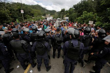 Hondura's police officers stand as Honduran migrants look on near of Agua Caliente while hoping to cross into Guatemala and join a caravan trying to reach the U.S., in Honduras October 17, 2018. REUTERS/Jorge Cabrera