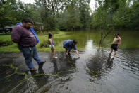 Cal Kingsmill, Jr., and his wife Jessie Kingsmill, point out crickets to their children Marina, 8, and Raylan, 8, in the receding floodwater in front of their home, after Tropical Storm Claudette passed through, in Slidell, La., Saturday, June 19, 2021. The National Hurricane Center declared Claudette organized enough to qualify as a named storm early Saturday, well after the storm's center of circulation had come ashore southwest of New Orleans. (AP Photo/Gerald Herbert)