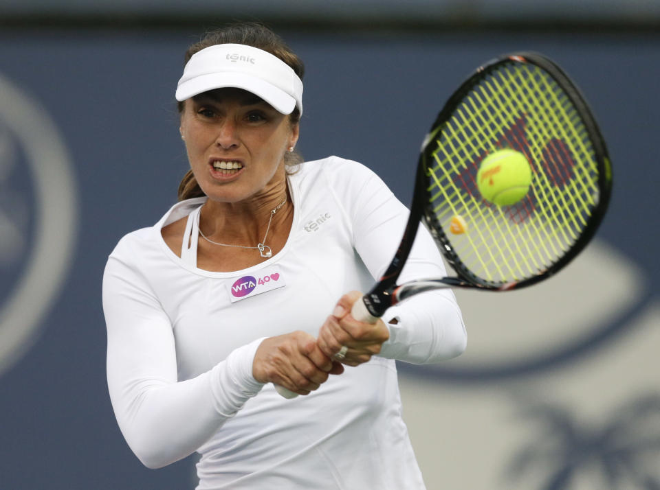 Martina Hingis, of Switzerland, hits a return during her doubles tennis match against Germany's Julia Goerges and Croatia's Darija Jurak at the Southern California Open tennis tournament Wednesday, July 31, 2013 in Carlsbad, Calif. (AP Photo/Chris Carlson)