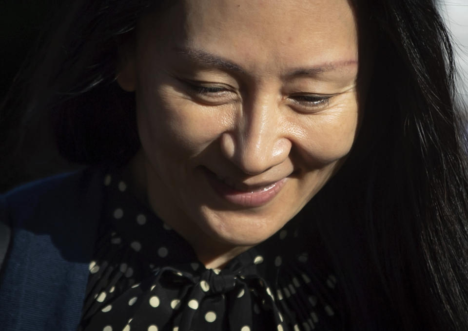 Meng Wanzhou, center, chief financial officer of Huawei Technologies, leaves her home in Vancouver, on Friday, Sept. 24, 2021. Wanzhou has resolved criminal charges against her as part of a deal with the U.S. Justice Department that could pave the way for her to return to China and that concludes a case that roiled relations between Washington and Beijing. (Darryl Dyck/The Canadian Press via AP)