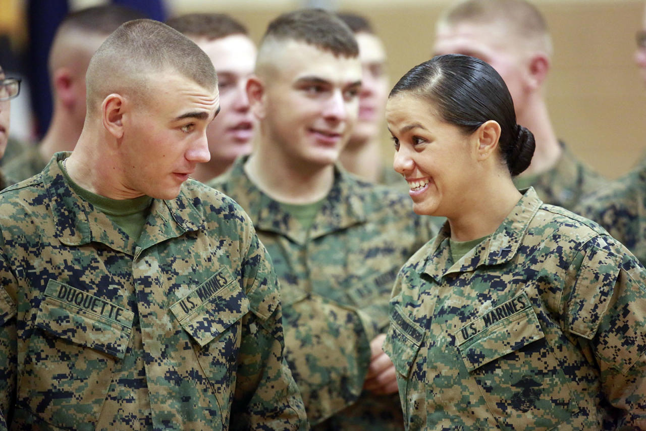 Private First Class Cristina Fuentes Montenegro, right, 25, shares a moment with a fellow Marine during graduation ceremony held on Camp Geiger, Jacksonville, Thursday, Nov. 21, 2013. Montenegro was one of three female Marines who became the first women to graduate from the Corps' tough-as-nails enlisted infantry training school in North Carolina. The three completed the rigorous 59-day course and met the same test standards as the men, said Marine Corps spokeswoman Capt. Geraldine Carey. (AP Photo/The Daily News, John Althouse)