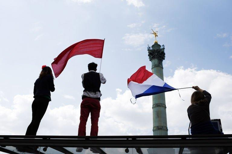 Protesters hold a France's national flag (R) and a red flag, on May 5, 2013 on the Bastille square in Paris, as they take part in a demonstration. Tens of thousands of protesters took to the streets of Paris on Sunday to mark Socialist President Francois Hollande's first year in office by accusing him of turning his back on the left