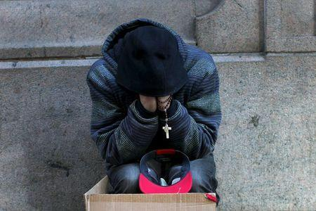 A homeless man sits along a sidewalk on East 42nd Street in the Manhattan borough of New York City, January 4, 2016. REUTERS/Mike Segar