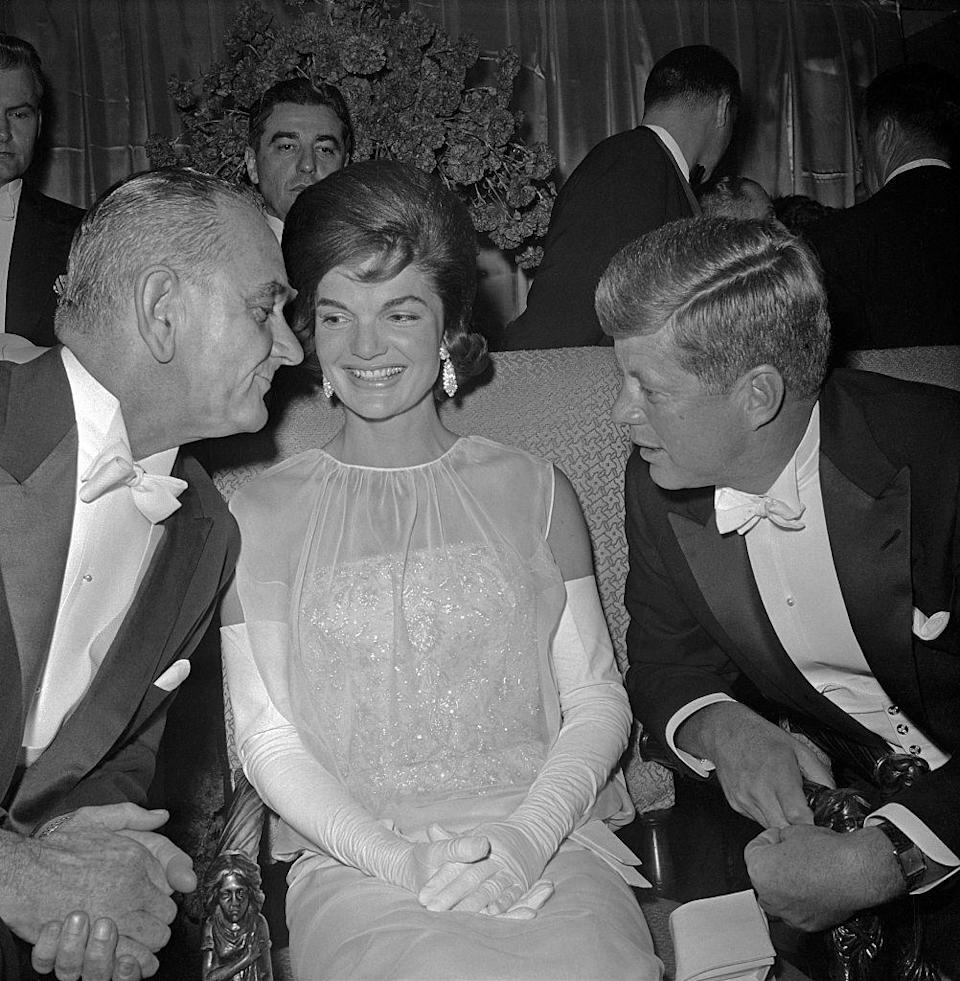 <p>While seated in the wings of the DC Armory, Vice President Lyndon B. Johnson speaks with the First Lady and President. Jacqueline Kennedy stunned in a white chiffon and sequin evening gown designed by Oleg Cassini. </p>