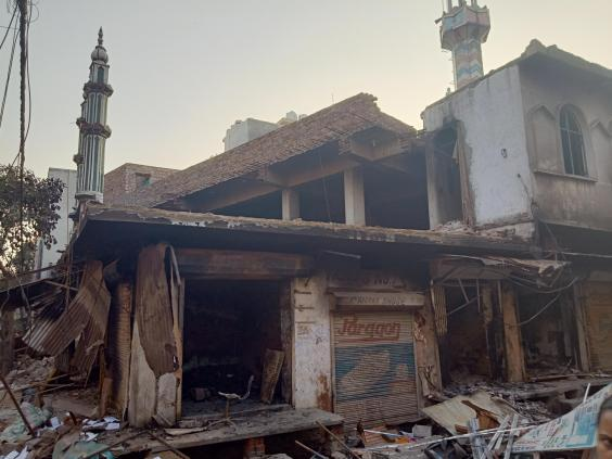 Muslim homes and businesses stand broken and charred next to attacked mosque (Adam Withnall/The Independent)