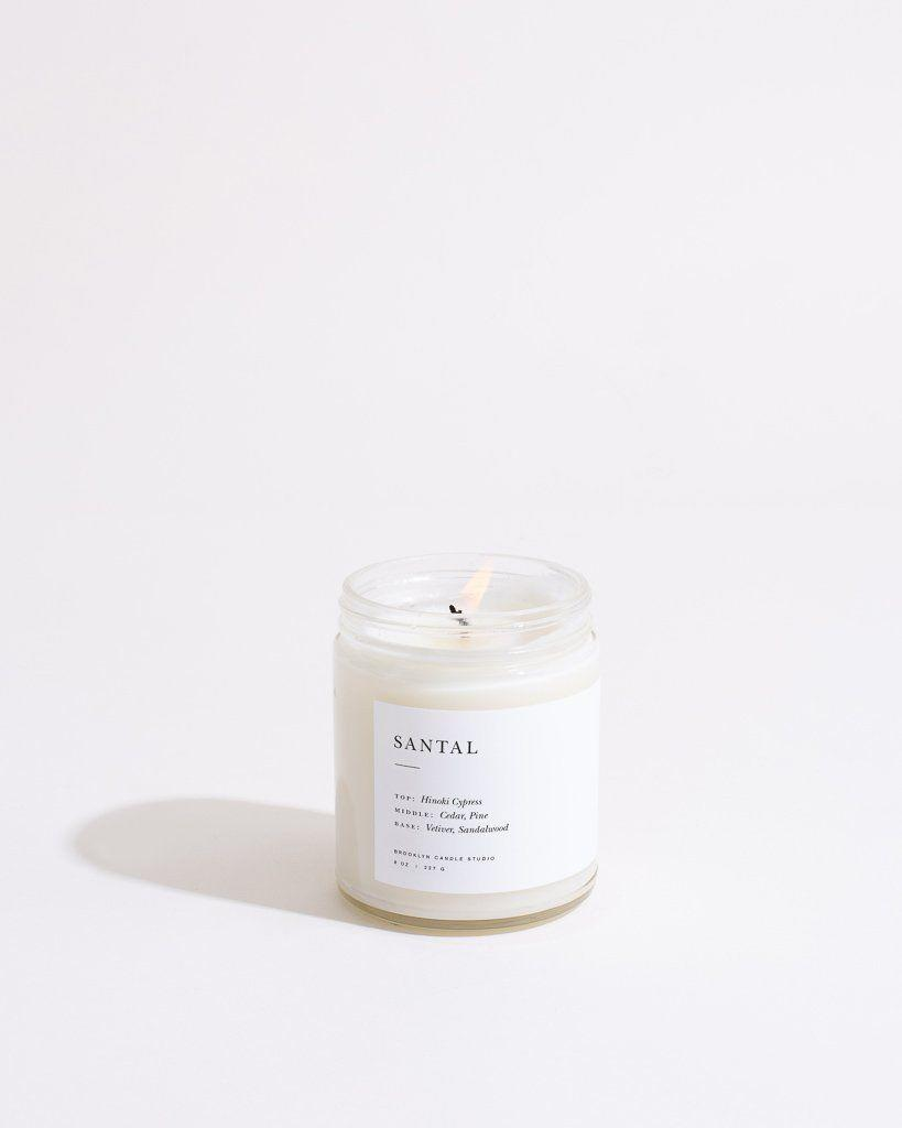 """<p><strong>Brooklyn Candle Studio</strong></p><p>brooklyncandlestudio.com</p><p><strong>$28.00</strong></p><p><a href=""""https://go.redirectingat.com?id=74968X1596630&url=https%3A%2F%2Fbrooklyncandlestudio.com%2Fcollections%2Fsingle-candles%2Fproducts%2Fsantal-minimalist-candle&sref=https%3A%2F%2Fwww.goodhousekeeping.com%2Flife%2Fentertainment%2Fg34862781%2Fbest-scented-candles%2F"""" rel=""""nofollow noopener"""" target=""""_blank"""" data-ylk=""""slk:Shop Now"""" class=""""link rapid-noclick-resp"""">Shop Now</a></p><p>This candle is made from 100% soy wax, and is ideal for people who love earthy scents, such as Hinoki Cypress, sandalwood, and pine. </p>"""