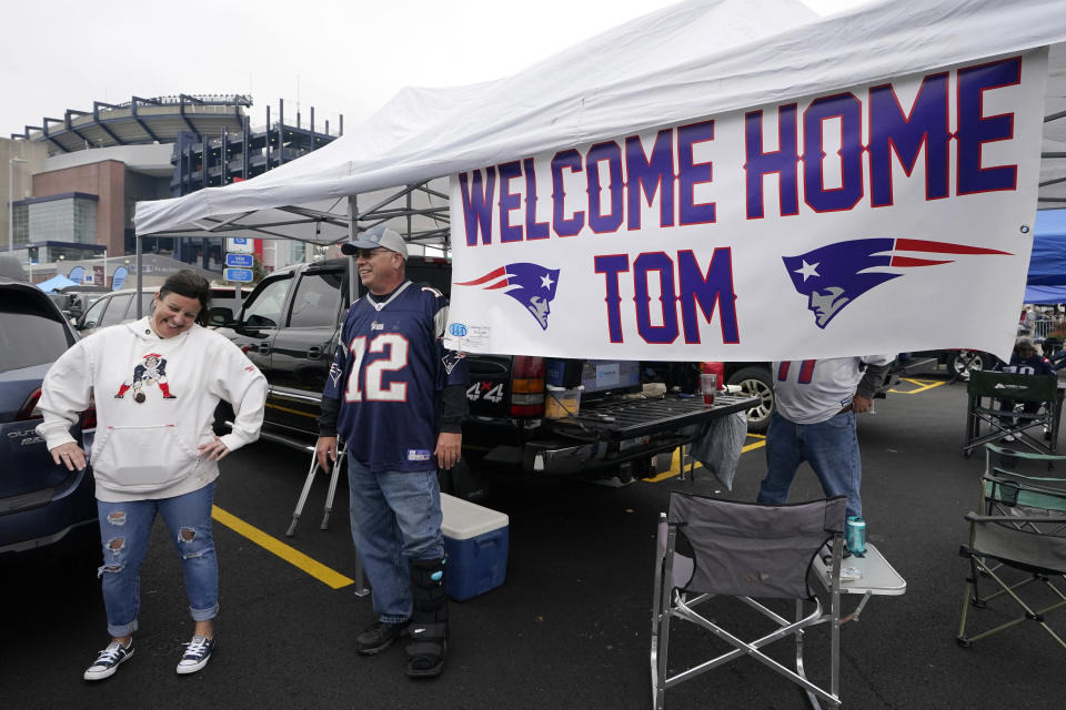 New England Patriots fan Stephanie Lamontagne, left, of Merrimack, N.H. smiles while chatting with Bill Gately, of Burrillville, R.I., while tailgating near a sign greeting the return of quarterback Tom Brady prior to an NFL football game between the New England Patriots and Tampa Bay Buccaneers, Sunday, Oct. 3, 2021, in Foxborough, Mass. (AP Photo/Steven Senne)