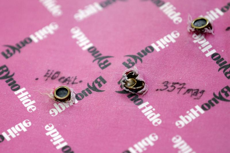 This Wednesday, Dec. 19, 2012 photo shows an anti- ballistic insert for a children's backpack pierced by .40 cal., left, and .357 mag. rounds at the Amendment ll manufacturing facility in Salt Lake City. Anxious parents reeling in the wake the Connecticut school shooting are fueling sales of armored backpacks for children emblazoned with Disney and Avengers logos, as firearms enthusiasts stock up on assault rifles nationwide amid fears of imminent gun control measures.  At Amendment II, sales of childrenís backpacks and armored inserts are up 300 percent. (AP Photo/Rick Bowmer)