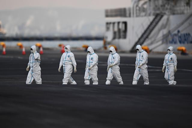 People wearing protective suits walk from the Diamond Princess cruise ship, with around 3,600 people quarantined onboard due to fears of the new coronavirus, at the Daikoku Pier Cruise Terminal in Yokohama port on February 10, 2020. - Around 60 more people on board the quarantined Diamond Princess cruise ship moored off Japan have been diagnosed with novel coronavirus, the country's national broadcaster said on February 10, raising the number of infected passengers and crew to around 130. (Photo by CHARLY TRIBALLEAU / AFP) (Photo by CHARLY TRIBALLEAU/AFP via Getty Images)