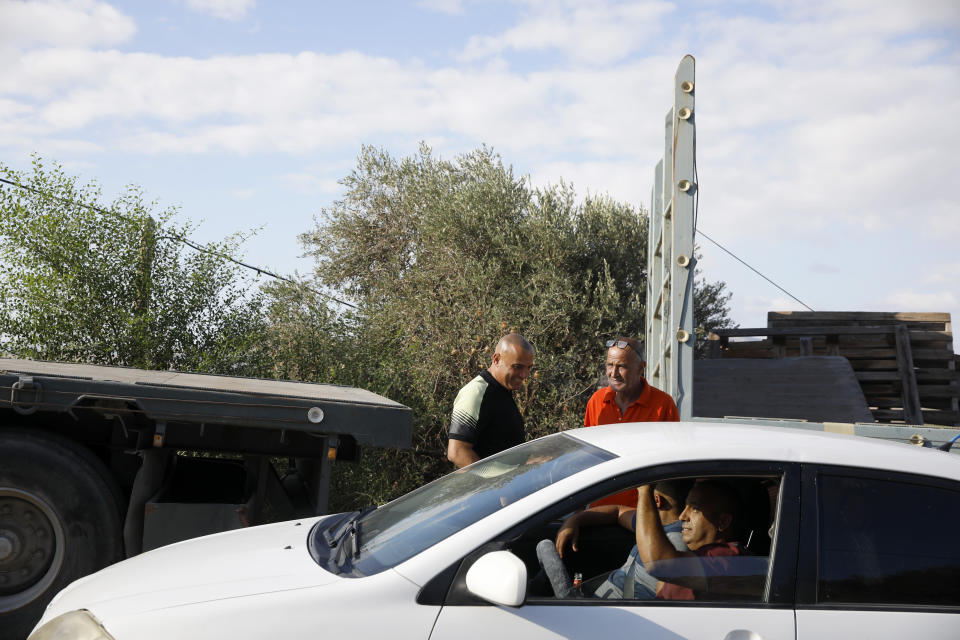 Locals gather near Palestinian fugitive Zakaria Zubeidi's hideouts in Umm al-Ghanam, northern Israel, Saturday, Sept. 11, 2021. Following Zubeidi's arrest, police said they have caught four of six Palestinians who broke out of a maximum-security prison early this week. (AP Photo/Ariel Schalit)
