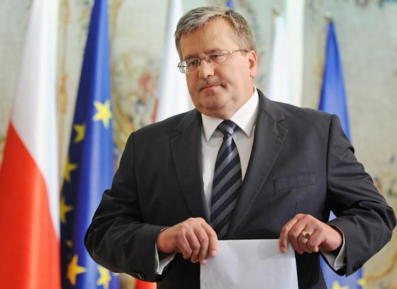 """Polish President Bronislaw Komorowski holds a copy of U.S. President Barack Obama's letter, as he leaves a press conference in Warsaw, Poland, Friday, June 1, 2012. Obama has written a letter to Komorowski expressing """"regret"""" for an inadvertent verbal gaffe that caused a storm controversy in Poland this week, after the U.S. President used the expression """"Polish death camp"""" , rather than """"Nazi death camp in German occupied Poland, while honoring a Polish WW II hero. (AP Photo/Alik Keplicz)"""