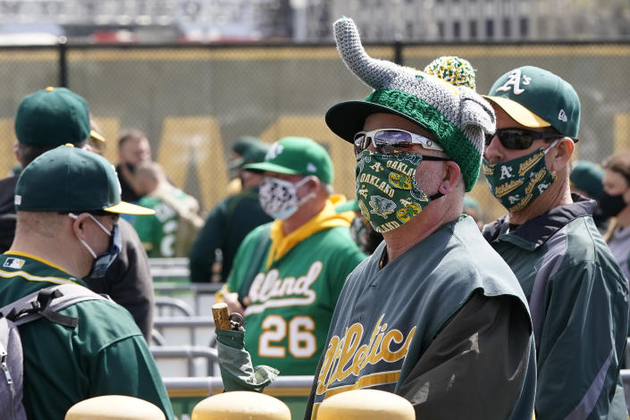 Oakland Athletics fans wearing face masks wait to enter a baseball game between the Athletics and the Houston Astros in Oakland, Calif., Saturday, April 3, 2021. (AP Photo/Jeff Chiu)