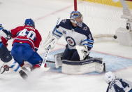 Montreal Canadiens' Joel Armia (40) scores a shorthanded goal on Winnipeg Jets goaltender Connor Hellebuyck (37) as Jets' Josh Morrissey (44) looks on during the second period of an NHL Stanley Cup playoff hockey game in Montreal, Sunday, June 6, 2021. (Ryan Remiorz/The Canadian Press via AP)