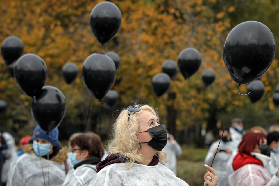 """FILE - In this Tuesday, Nov. 17, 2020 file photo, medical workers, wearing masks for protection against the COVID-19 infection, hold black balloons in memory of those who lost their lives while in the care of the state health system in Bucharest, Romania. After the European Union passed the death toll of half a million citizens lost to the coronavirus on Wednesday, Feb. 10, 2021, the EU Commission chief said that stalling rollout of the vaccines could be partly blamed on the bloc being over-optimistic, over-confident and plainly """"too late."""" (AP Photo/Vadim Ghirda, File)"""