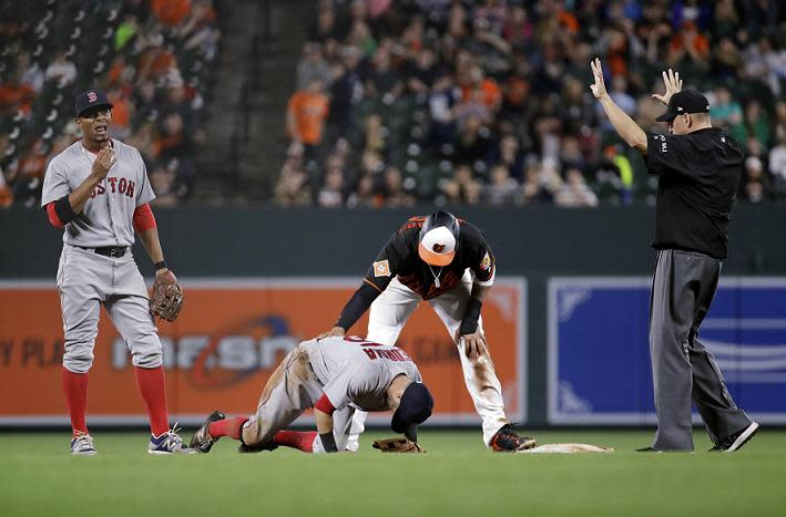 Red Sox second baseman Dustin Pedroia struggles to stand after a late slide from Baltimore's Manny Machado. (AP)