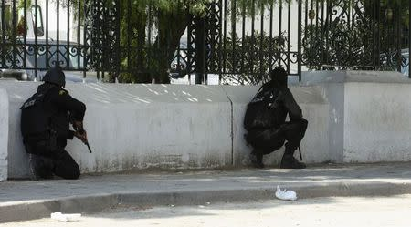 Police officers crouch on the pavement outside parliament in Tunis March 18, 2015. REUTERS/Zoubeir Souissi
