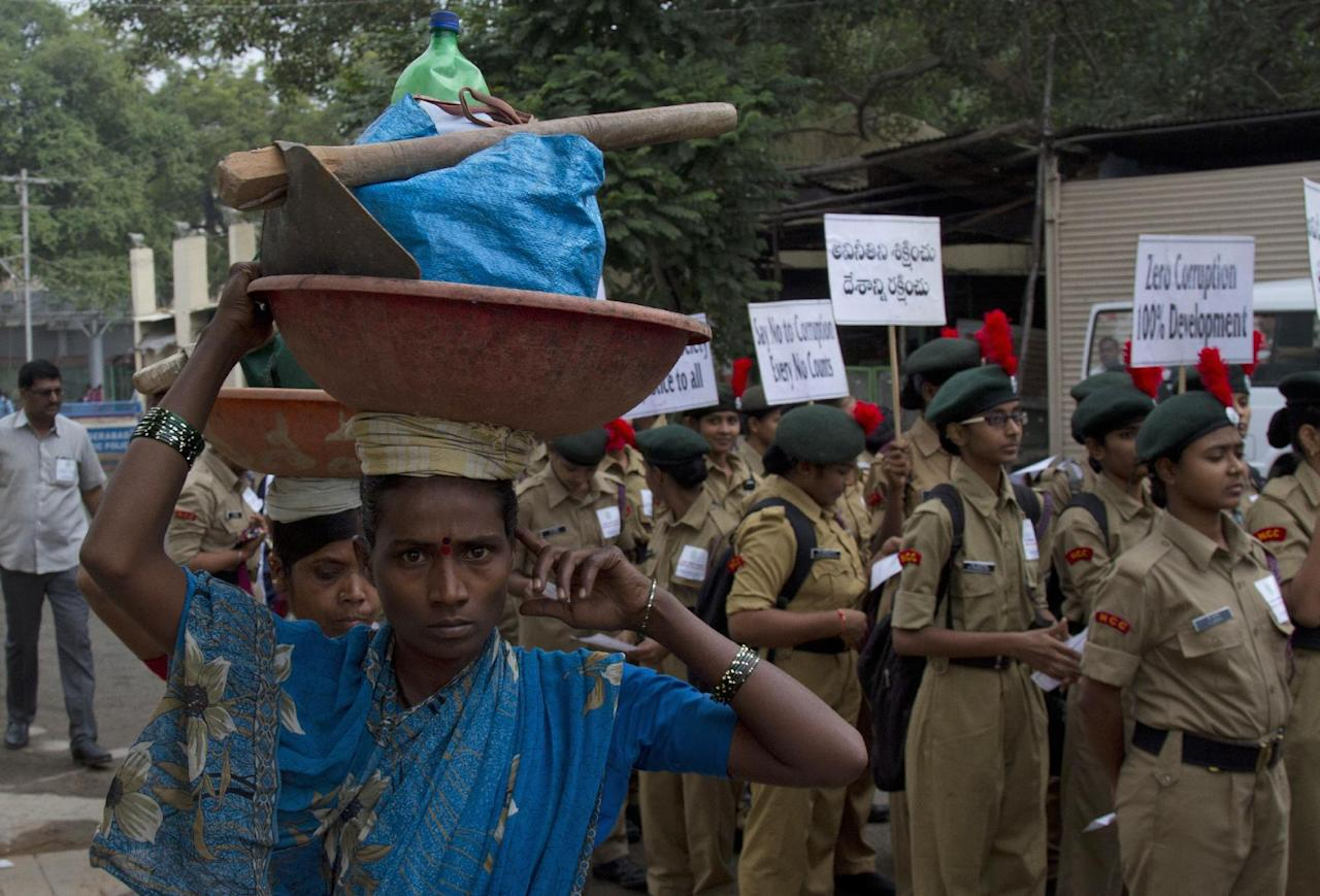 Indian laborers walk to work, past young activists participating in a protest against corruption in Hyderabad, India ,Saturday, Dec. 3, 2016. International Anti-Corruption Day is marked annually on Dec. 9. (AP Photo /Mahesh Kumar A.)