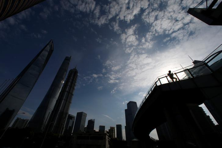 A man walks on a bridge in the financial district of Pudong in Shanghai,