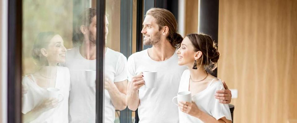 Young and happy couple dressed in white shirts standing together with cups near the window at home