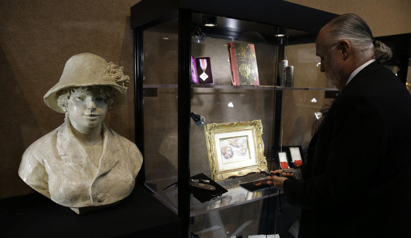 In this photo made Friday, Aug. 16, 2013, Brian Roughton, managing director of fine art at the Heritage Auctions, opens a case displaying items from the personal archives of artist Pierre-Auguste Renoir in Dallas. The French artist's personal archive will be up for sale in New York City in September. (AP Photo/LM Otero)