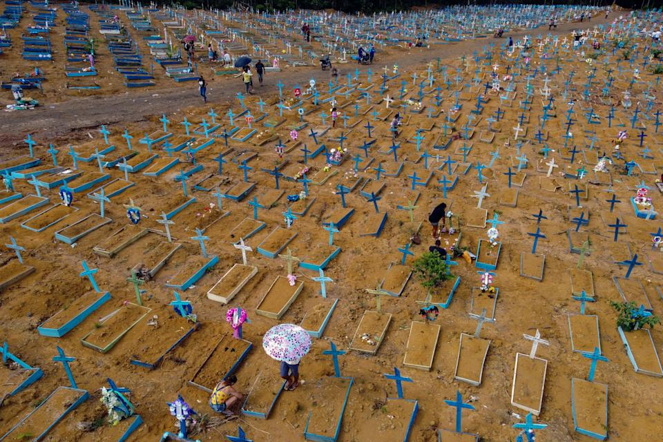 TOPSHOT - People visit the Nossa Senhora Aparecida cemetery on Mothers Day, in Manaus, Amazonas State, Brazil, on May 9, 2021, amid the COVID-19 novel coronavirus pandemic. - Cemeteries in Brazil opened this weekend for the first time for the general public since the start of the COVID-19 pandemic. (Photo by Michael DANTAS / AFP) (Photo by MICHAEL DANTAS/AFP via Getty Images)