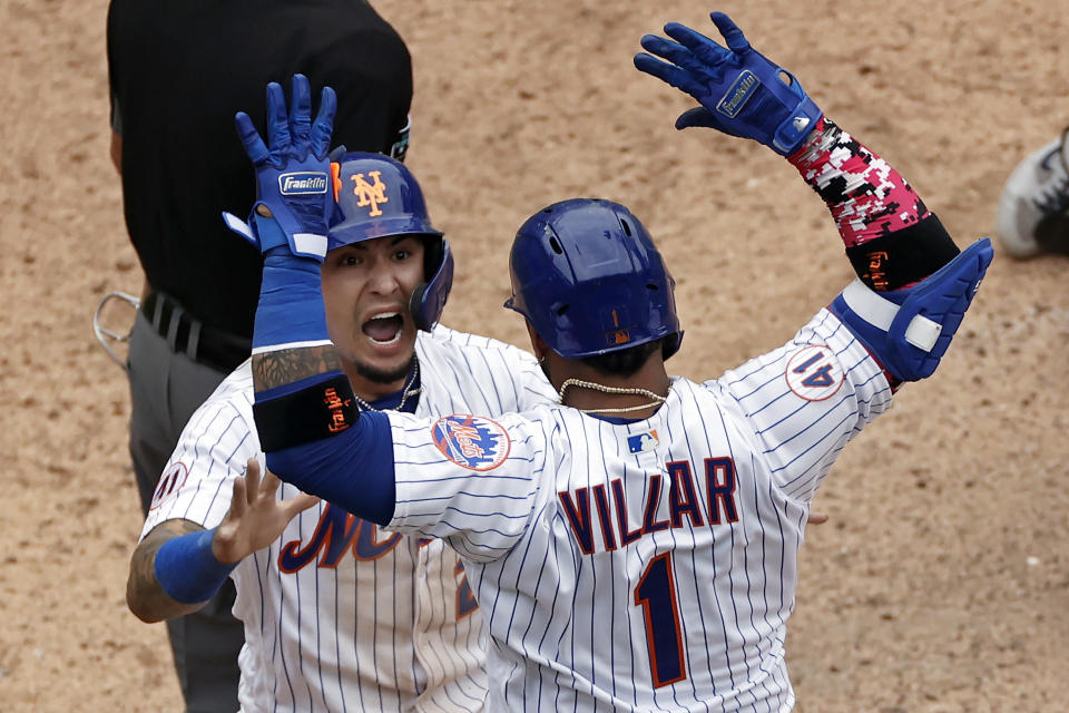 New York Mets' Javier Baez celebrates with Jonathan Villar after scoring the game winning run against the Miami Marlins during the ninth inning of the first game of a baseball doubleheader that started April 11 and was suspended because of rain, Tuesday, Aug. 31, 2021, in New York. The Mets won 6-5. (AP Photo/Adam Hunger)