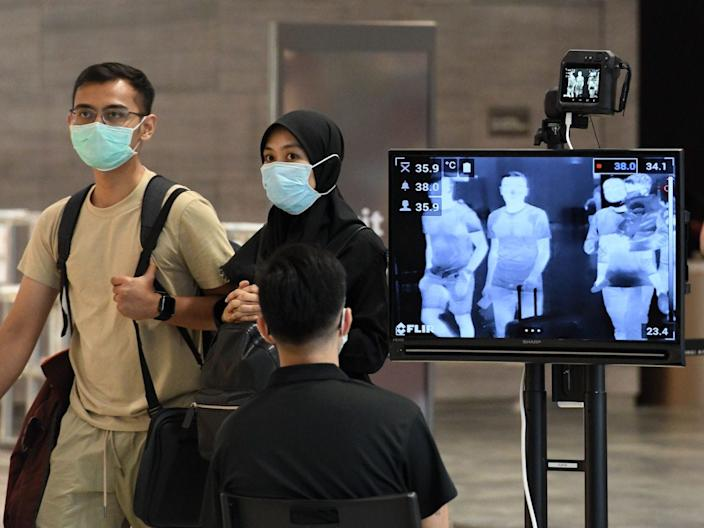 A couple walk past a temperature screening check at Changi International Airport in Singapore on February 27, 2020.