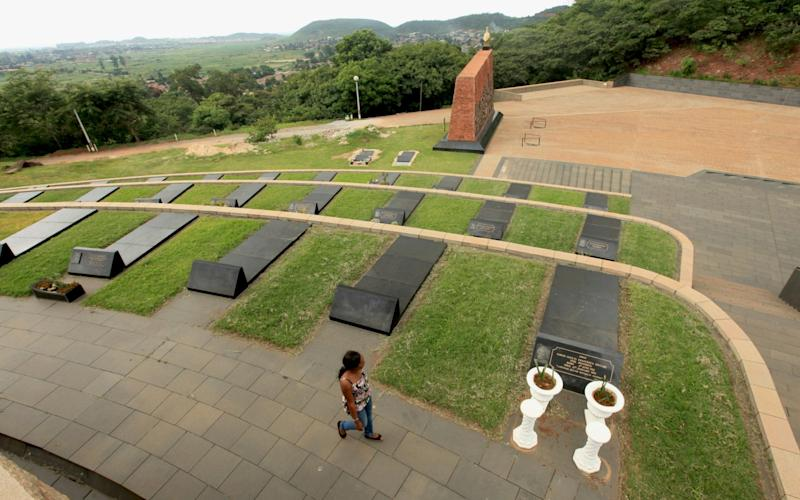 A woman walks past rows of graves at the National Heroes Acre in Harare - AP