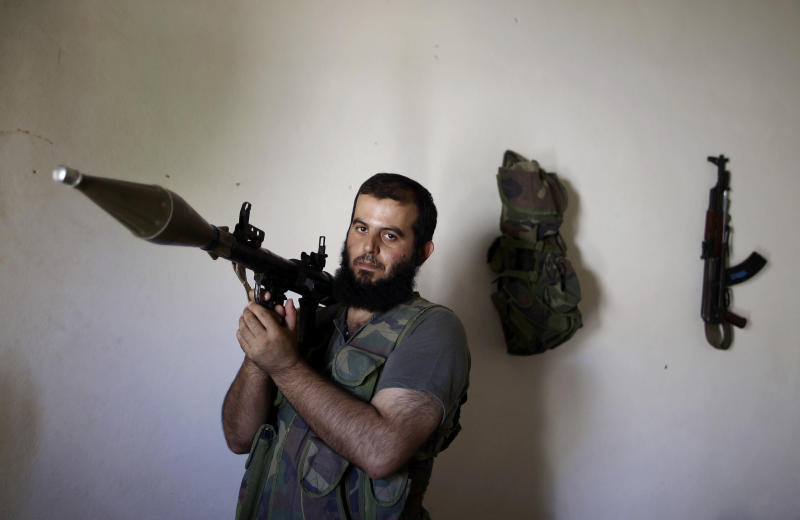 In this Tuesday, Sept. 4, 2012, photo, Syrian rebel fighter, Abu Muslim, 30, a former librarian, poses for a picture at a house where he and others wait their turn to go and fight against government forces in Aleppo, in Marea on the outskirts of Aleppo city, Syria. Syria's rebels have turned to a new tactic of attacking bases, trying to stop the jets and attack helicopters that have wreaked devastation on their fighters and civilians in the battleground city of Aleppo and the nearby countryside. Abu Muslim became a specialist in rocket-propelled grenades during his military service a decade ago. He said in the tight confines of urban warfare, taking out the regime's older tanks, wasn't a problem.(AP Photo/Muhammed Muheisen)