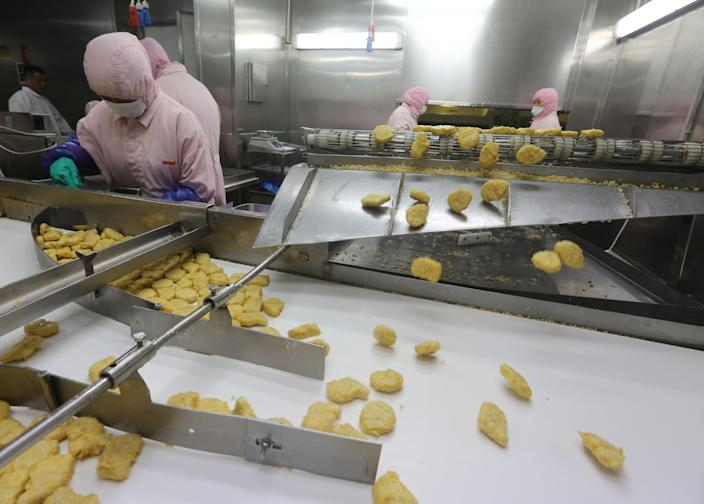 Workers produce food at the Shanghai Husi Food Co., a factory of US food provider OSI Group, in Shanghai, July 20, 2014 (AFP Photo/)