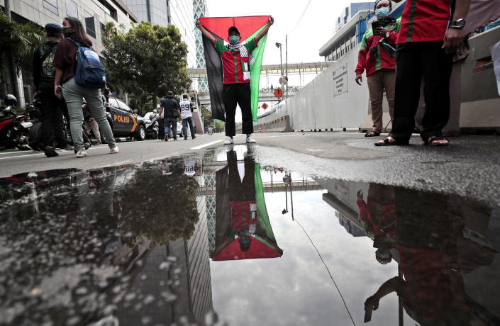 An image of a protester holding up a Palestinian flag is reflected in water on a street as he poses for photographers during a rally condemning Israeli attacks on the Palestinians, in Jakarta, Indonesia, Tuesday, May 18, 2021. (AP Photo/Dita Alangkara)
