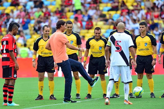In this photo released by Fotojump, Spaniard Rafael Nadal, third left, kicks the ball before the soccer game between Flamengo and Vasco at the Maracana stadium in Rio de Janeiro, Brazil, Sunday, Feb.16, 2014. Nadal is in Brazil to play in the Rio Open ATP tennis tournament. (AP Photo/Fotojump, Joao Pires)