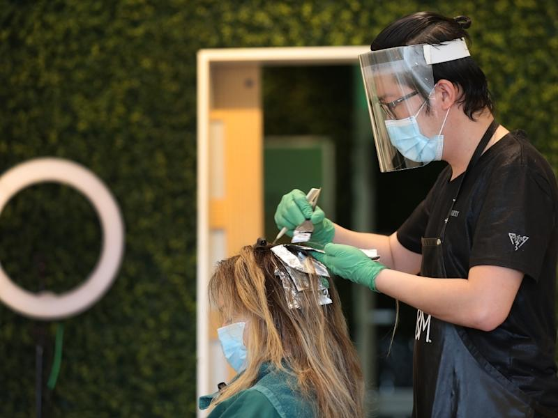Son Chau works on the hair of Christina Renbic after the Katon Salon reopened Monday in Fort Lauderdale.