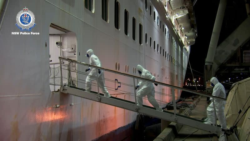 NSW Police personnel in personal protective equipment board the Ruby Princess during the Strike Force Bast raid of the cruise ship at Port Kembla