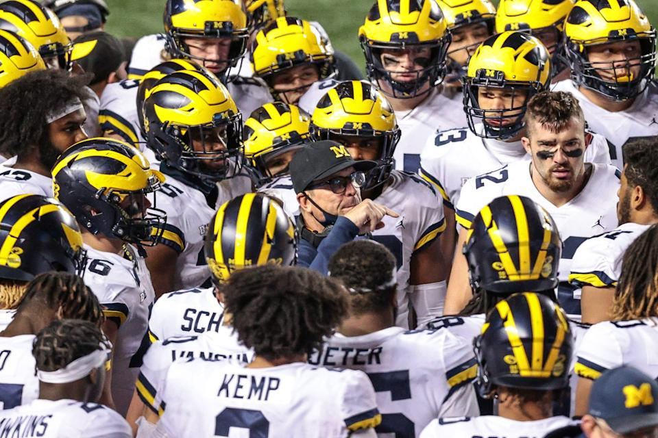 Michigan Wolverines head coach Jim Harbaugh talks with his team before overtime begins Nov. 21, 2020, against the Rutgers Scarlet Knights at SHI Stadium.