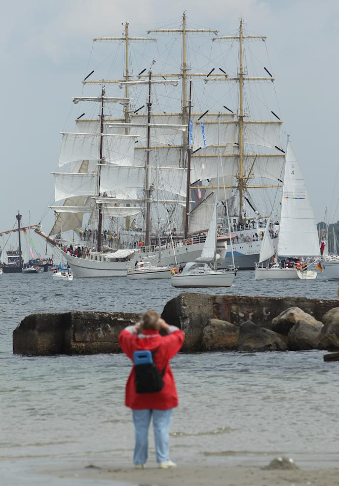 KIEL, GERMANY - JUNE 23:  A woman watches the Windjammer Parade of tall ships on June 23, 2012 in Kiel, Germany. The parade, which features approximately 100 tall ships and traditional large sailing ships, is the highlight of the Kieler Woche annual sailing festival, which this year is celebrating its 130th anniversary and runs from June 16-24.  (Photo by Sean Gallup/Getty Images)