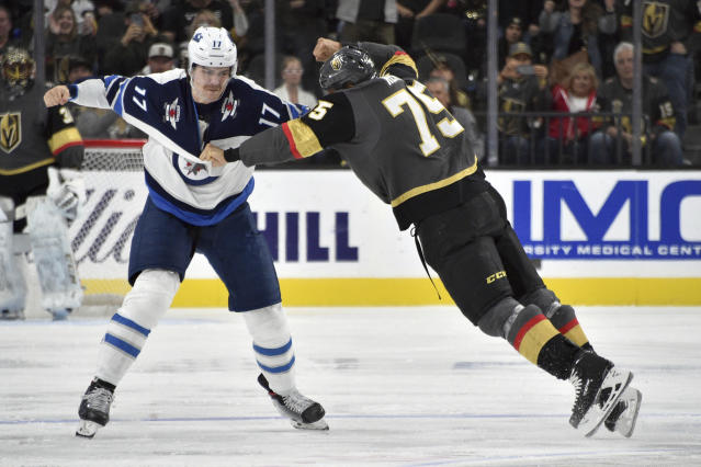 Winnipeg Jets center Adam Lowry (17) fights Vegas Golden Knights right wing Ryan Reaves during the second period of an NHL hockey game Saturday, Nov. 2, 2019, in Las Vegas. (AP Photo/David Becker)