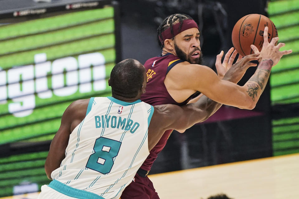 Charlotte Hornets' Bismack Biyombo (8) puts pressure on Cleveland Cavaliers' JaVale McGee during the first half of an NBA basketball game Wednesday, Dec. 23, 2020, in Cleveland. (AP Photo/Tony Dejak)